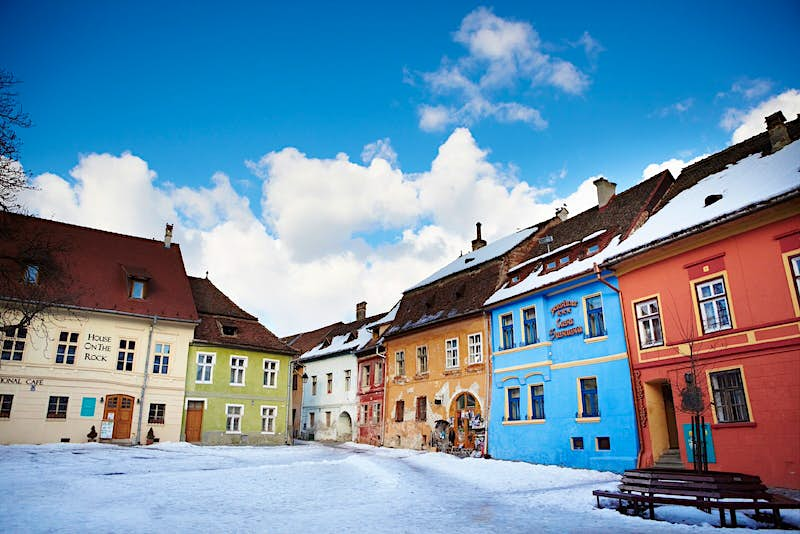 A snowy square of colourful houses in Sighişoara, Transylvania.