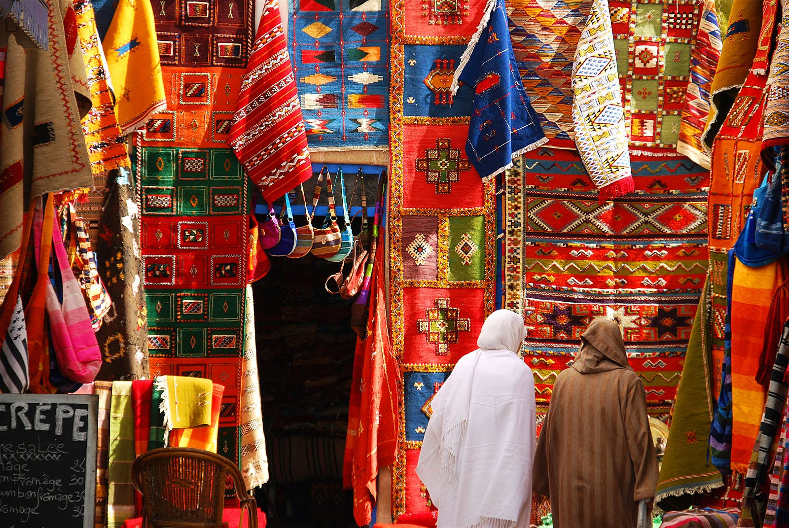 Women wandering through the Carpet Market in Essaouira, Morocco. Image by leuntje / Getty Images
