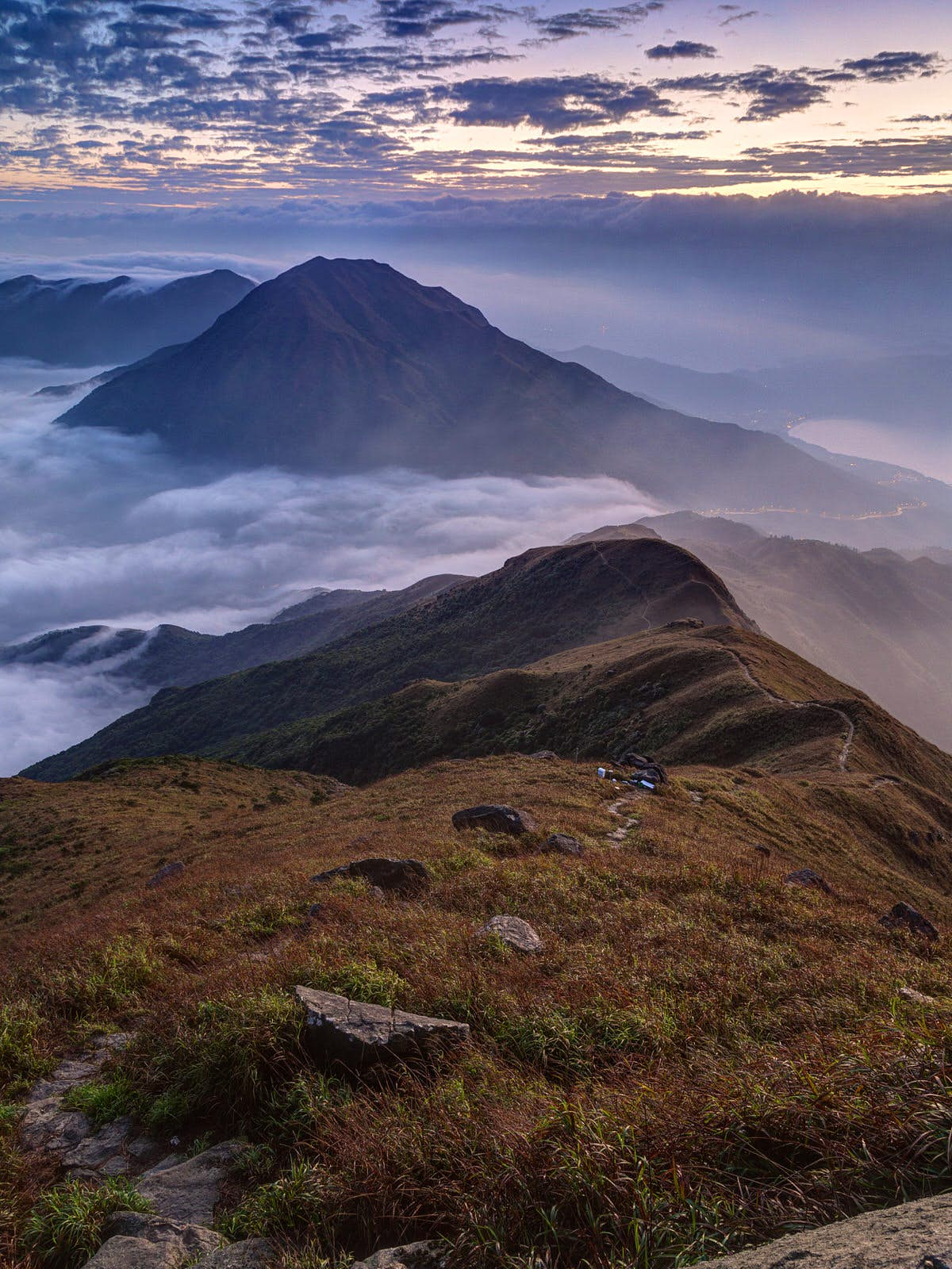 Clouds rolling over mountain on Lantau Island, viewed from the Lantau Peak (the second highest peak in Hong Kong, China) at dawn.