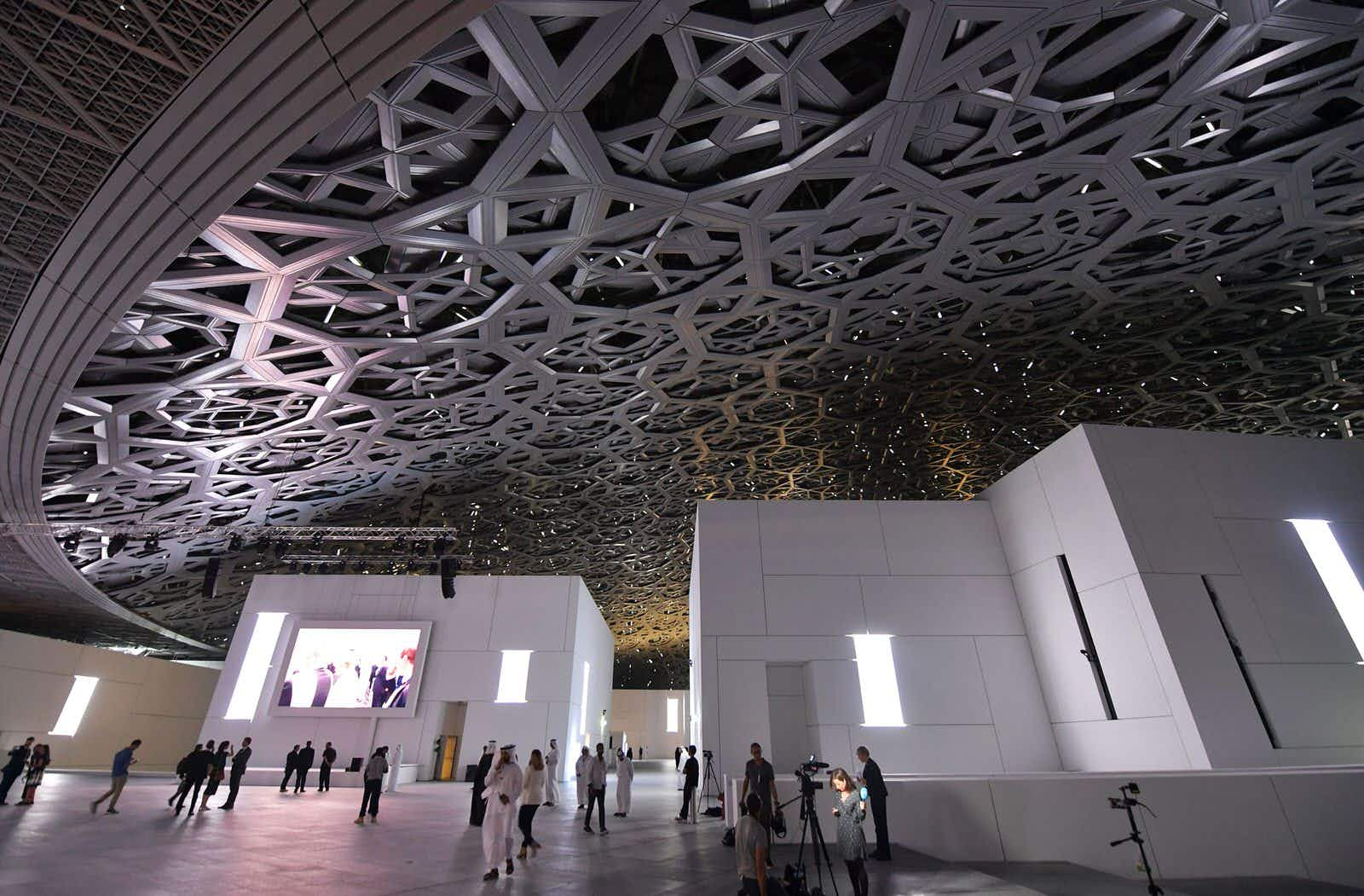 A general view shows people walking under the dome at the Louvre Abu Dhabi Museum that was designed by French architect Jean Nouvel during its inauguration on November 8, 2017 on Saadiyat island in the Emirati capital. More than a decade in the making, the Louvre Abu Dhabi opened its doors, bringing the famed name to the Arab world for the first time. / AFP PHOTO / ludovic MARIN / RESTRICTED TO EDITORIAL USE - MANDATORY MENTION OF THE ARTIST UPON PUBLICATION - TO ILLUSTRATE THE EVENT AS SPECIFIED IN THE CAPTION        (Photo credit should read LUDOVIC MARIN/AFP/Getty Images)