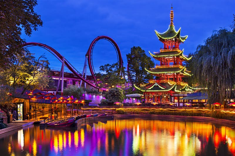 The amusement park at the Tivoli Gardens, Copenhagen; we see a lake in the foreground reflecting the illuminations from a Japanese-style pagoda and a rollercoaster with loops.