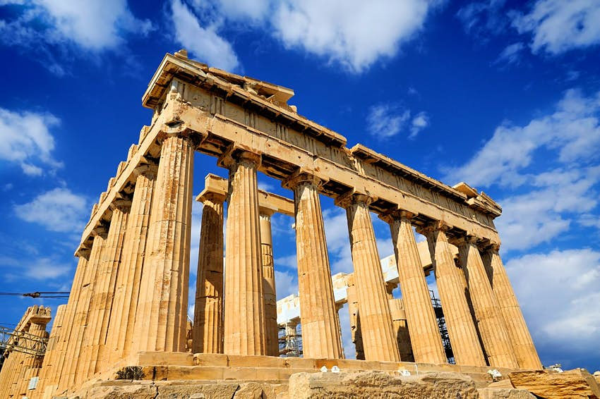 A close view of the fluted Doric columns of the Parthenon temple on a sunny day in Athens, Greece.
