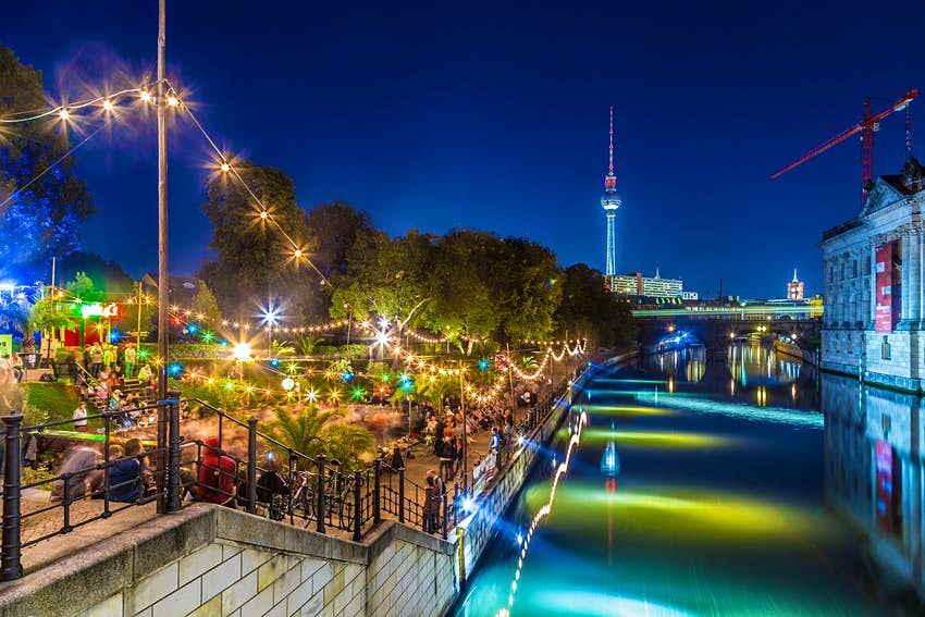 Revellers congregating on the banks of the Spree River at dusk in Berlin Mitte district