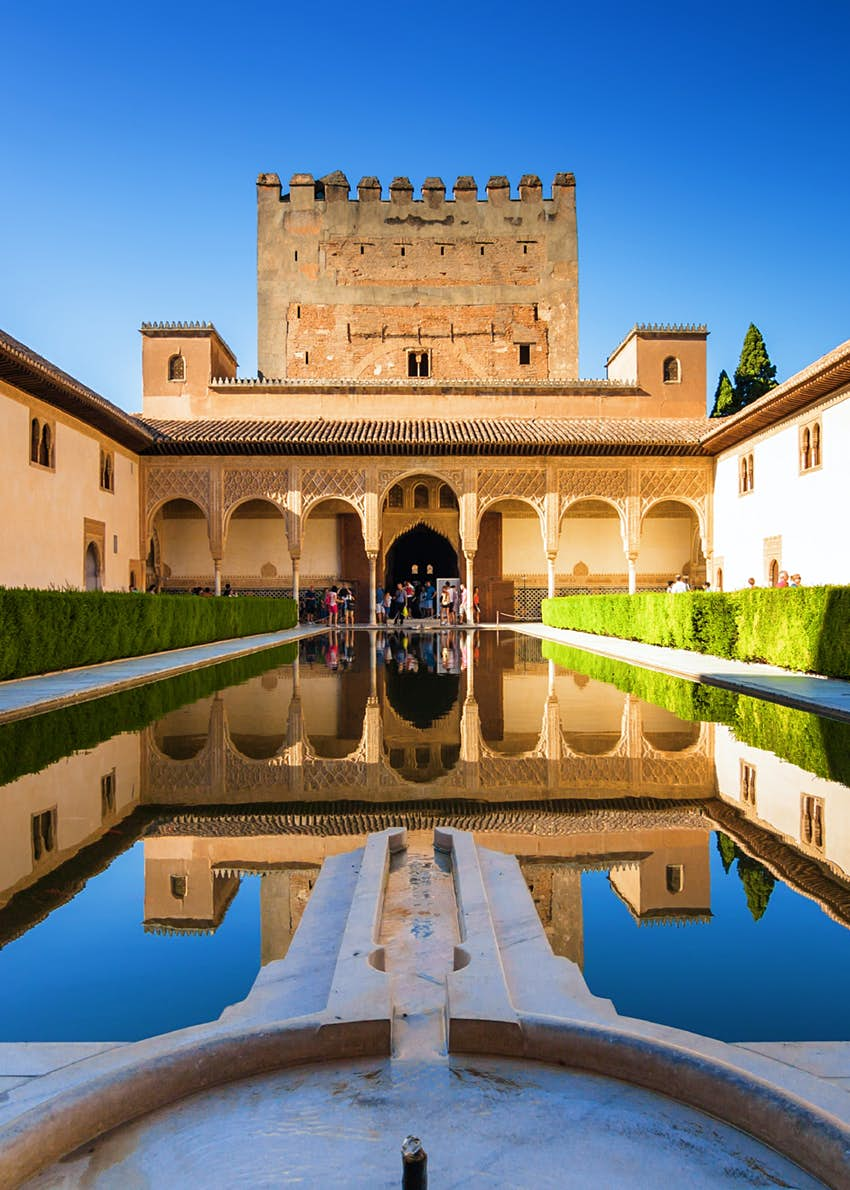 Part of the Alhambra complex - a Moorish-inspired fort with a graceful cloister in the foreground - reflects off the courtyard pool in Generalife Gardens, Granada, Spain.