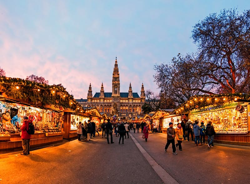 Christmas market at sunset in Vienna, Austria; shoppers are browsing stalls on either side of the road, while at the end is an imposing building with spires.