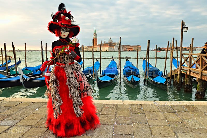 Masked reveller dressed in red, white and black in Venice, Italy, with a row of gondolas behind them and the city skyline on the other side of the water.