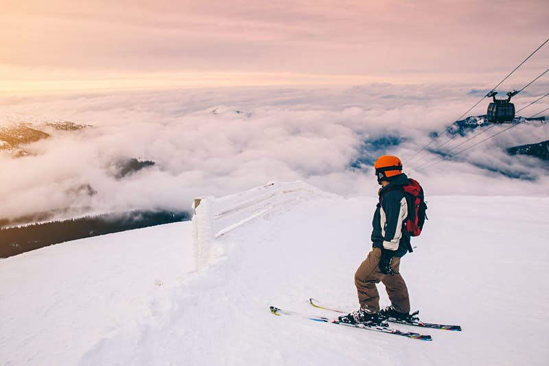 Skier at the summit of a mountain in Slovakia; there is cloud cover below and a chairlift rising to the right.