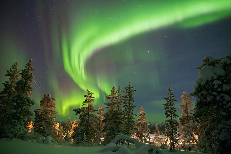The Northern Lights are a green swirl above a snowy forest in Abisko, Sweden.