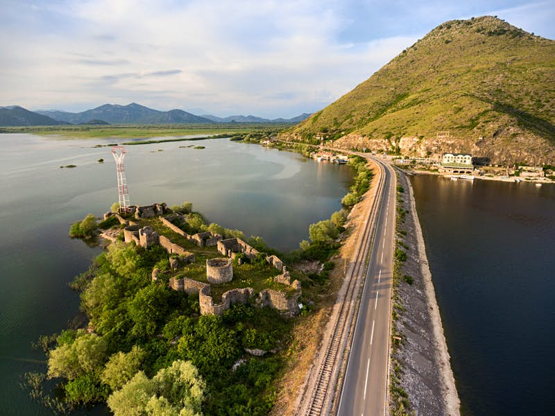 The train skirts the Lesendro Fortress ruins on Lake Skadar on its way to the Adriatic