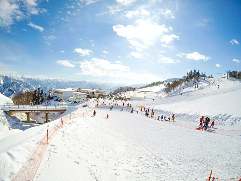 View of skiing on a wide snow-covered ski run on a clear day at Gala Yuzawa ski resort