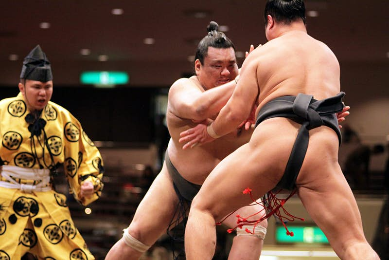 Two sumo wrestlers fight with each other in the ring as the umpire looks on