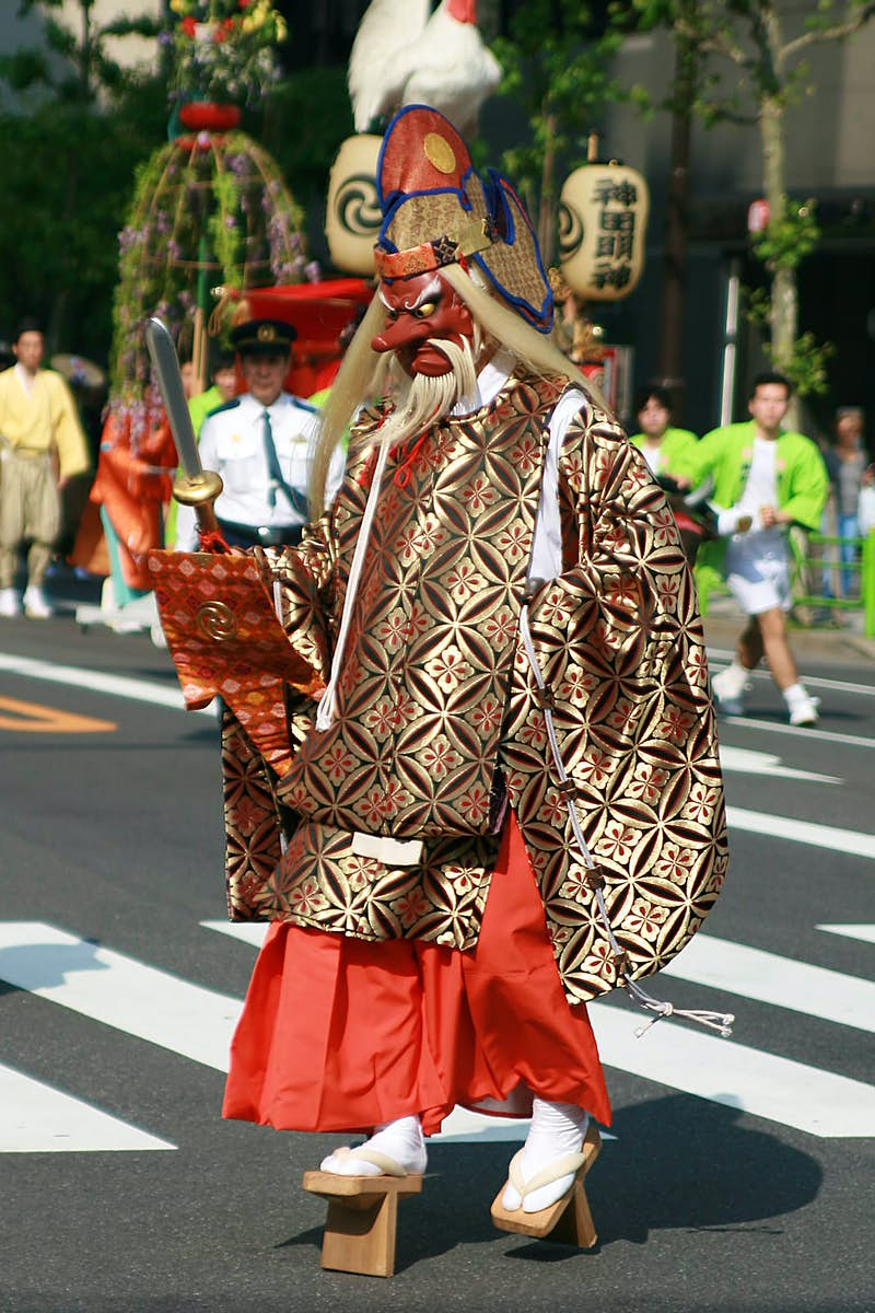 A person dressed in an elaboarate Tengū costume and mask walking across a street in Japan