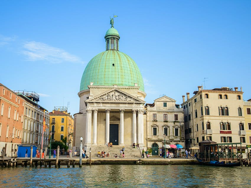The dome of the Chiesa di San Simeone Piccolo is hard to overlook as it pierces into a clear blue sky sitting above the dark reflective waters of the canals in Santa Croce - Lonely Planet © red-feniks / Shutterstock