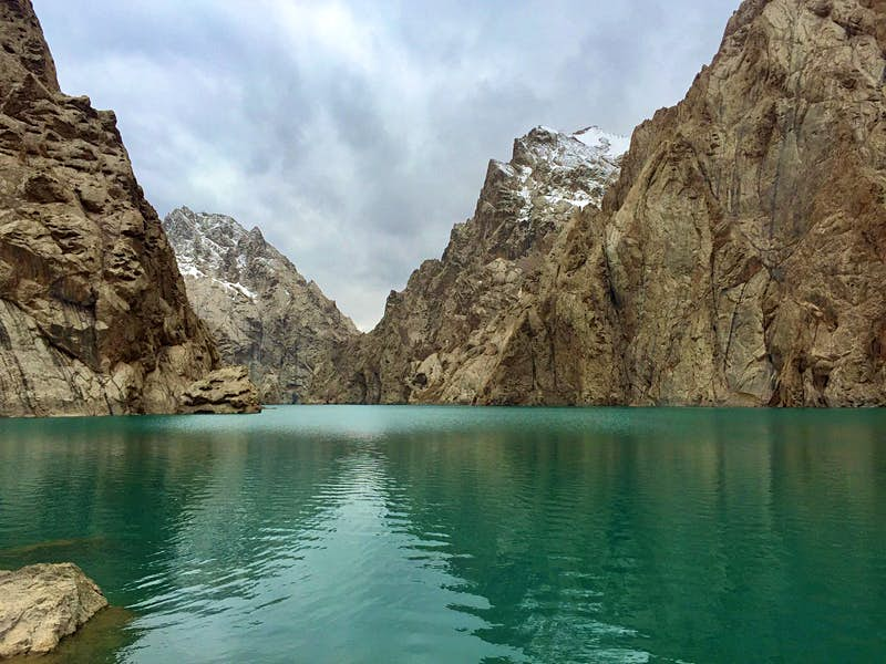 A turquoise lake framed by sharp grey mountain peaks and white snow clouds © Megan Eaves / Lonely Planet
