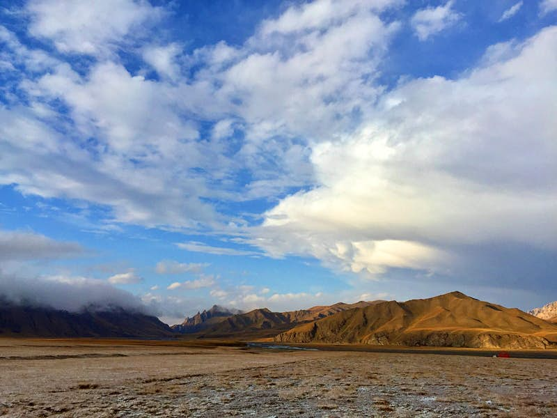 Wide landscape shot of brown mountains, a valley dusted with snow and blue sky dotted with white clouds © Megan Eaves / Lonely Planet