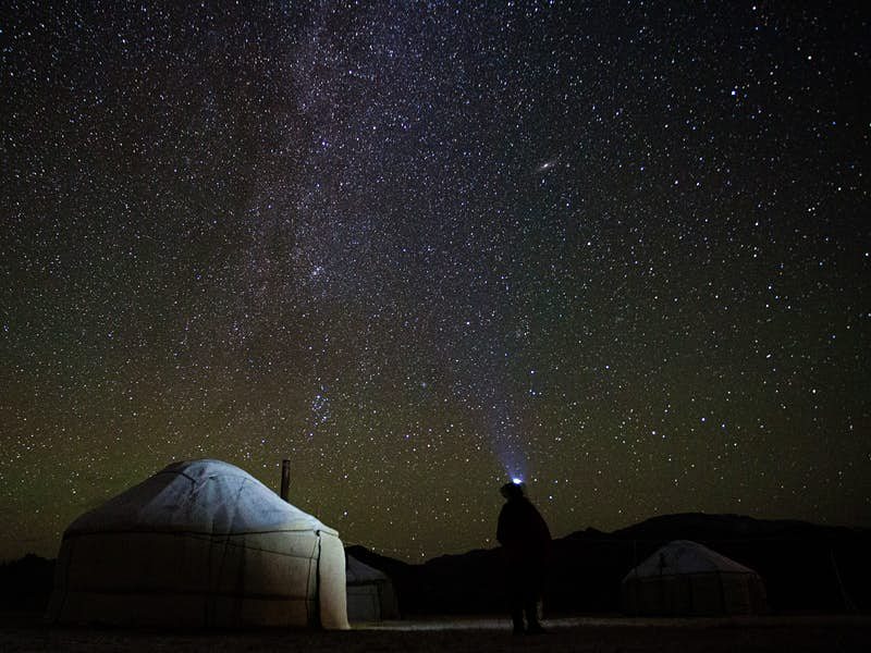 Night sky full of stars. In front, a semi-illuminated yurt tent and a person standing looking upwards with a head torch glowing. © Stephen Lioy / Lonely Planet