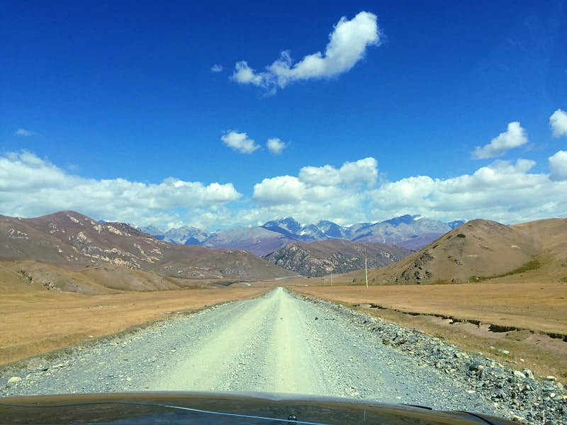 View through the windscreen of an SUV onto a wide dirt road leading into mountains, with blue sky above © Megan Eaves / Lonely Planet