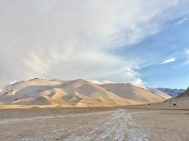 Tan and brown mountains in the distance with a light dusting of white snow, and white clouds above © Megan Eaves / Lonely Planet