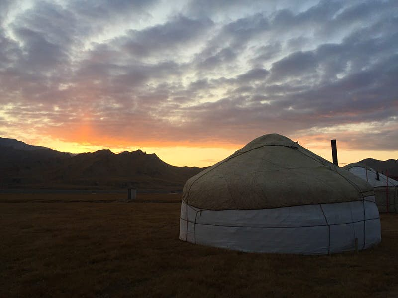A pink and yellow sunset outlines mountains behind a white yurt tent with small chimney © Megan Eaves / Lonely Planet