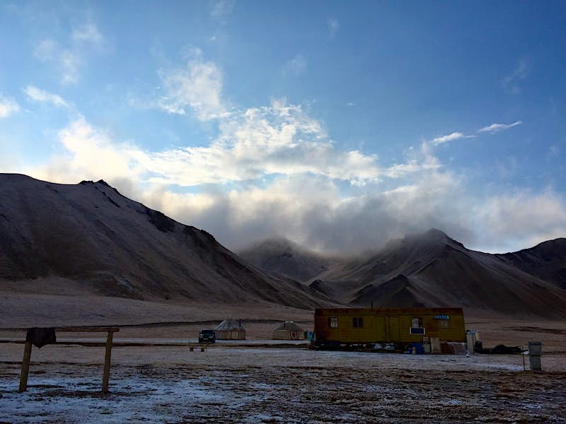 A yellow wagon and hitching post in front of several white yurts, with mountains and fog in the distance © Megan Eaves / Lonely Planet