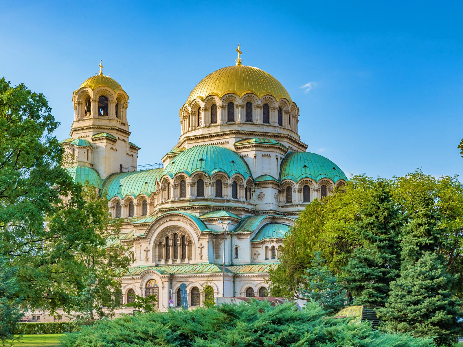 A large white church with several domed roofs in gold and teal colours