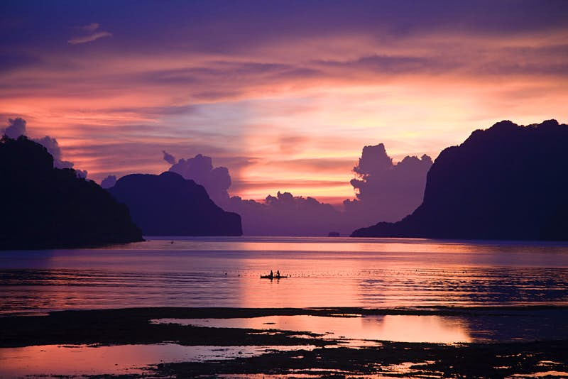 Two people on a kayak crossing Bacuit Bay, Palawan, at sunset ©Mark Watson/Highlux / Getty Images