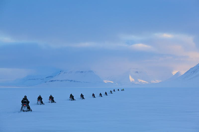 A group of people on snowmobiles exploring Svalbard ©Ethan Welty / Getty Images