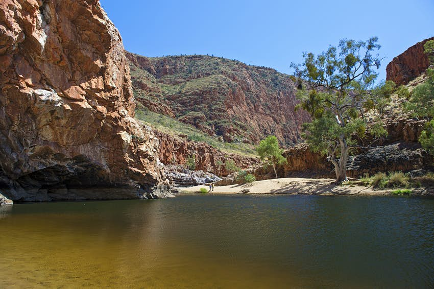 Ormiston Gorge, West MacDonnell National Park, Northern Territory. Pictured on a sunny day, the still body of water is surrounded by deep red sands and earth. Two people are walking away from the waters edge. There is blue sky and a few sparse trees in the background.