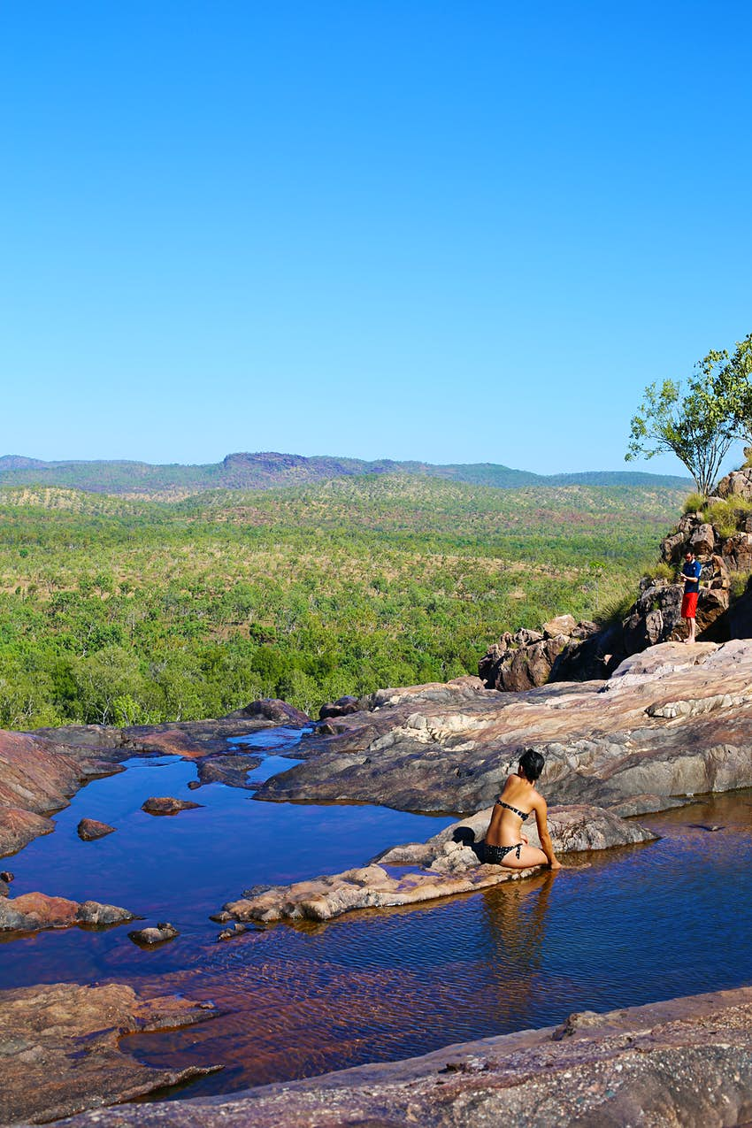 Gunlom Falls upper pools Northern Territory Australia. A woman sits an a small natural ledge between two pools wearing a black and white polka dot bikini, looking away from the camera. A man is standing in a pool further away, also looking away from the camera. It's a clear and sunny day