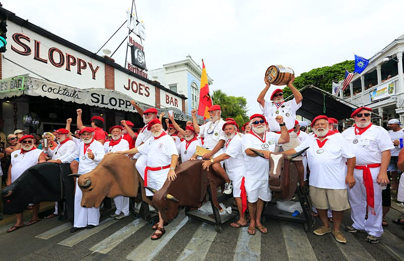 """Hemingway look-alikes attending """"Running of the Bulls"""" during the 35th annual Hemingway Days festival on the street of Key West with Sloppy Joe's Bar in the background."""