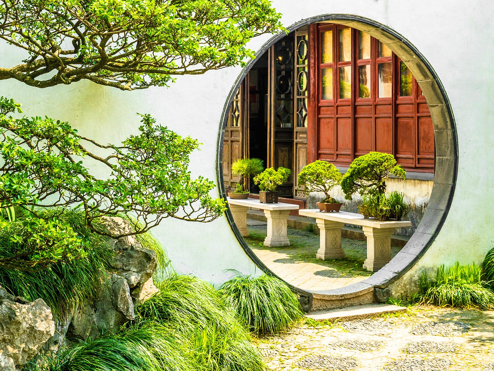 A round moon gate surrounded by white walls and green trees in Suzhou's the Garden of the Master of the Nets © Zharov Pavel / Shutterstock