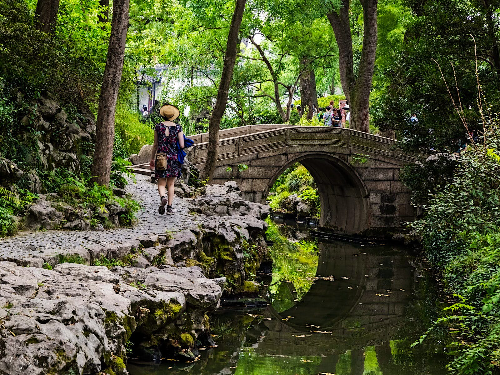 A tourist walks along a rocky forest path next to a pond with stone bridge. The serene paths of the Humble Administrator's Garden were restored in the 1950s © posztos / Shutterstock