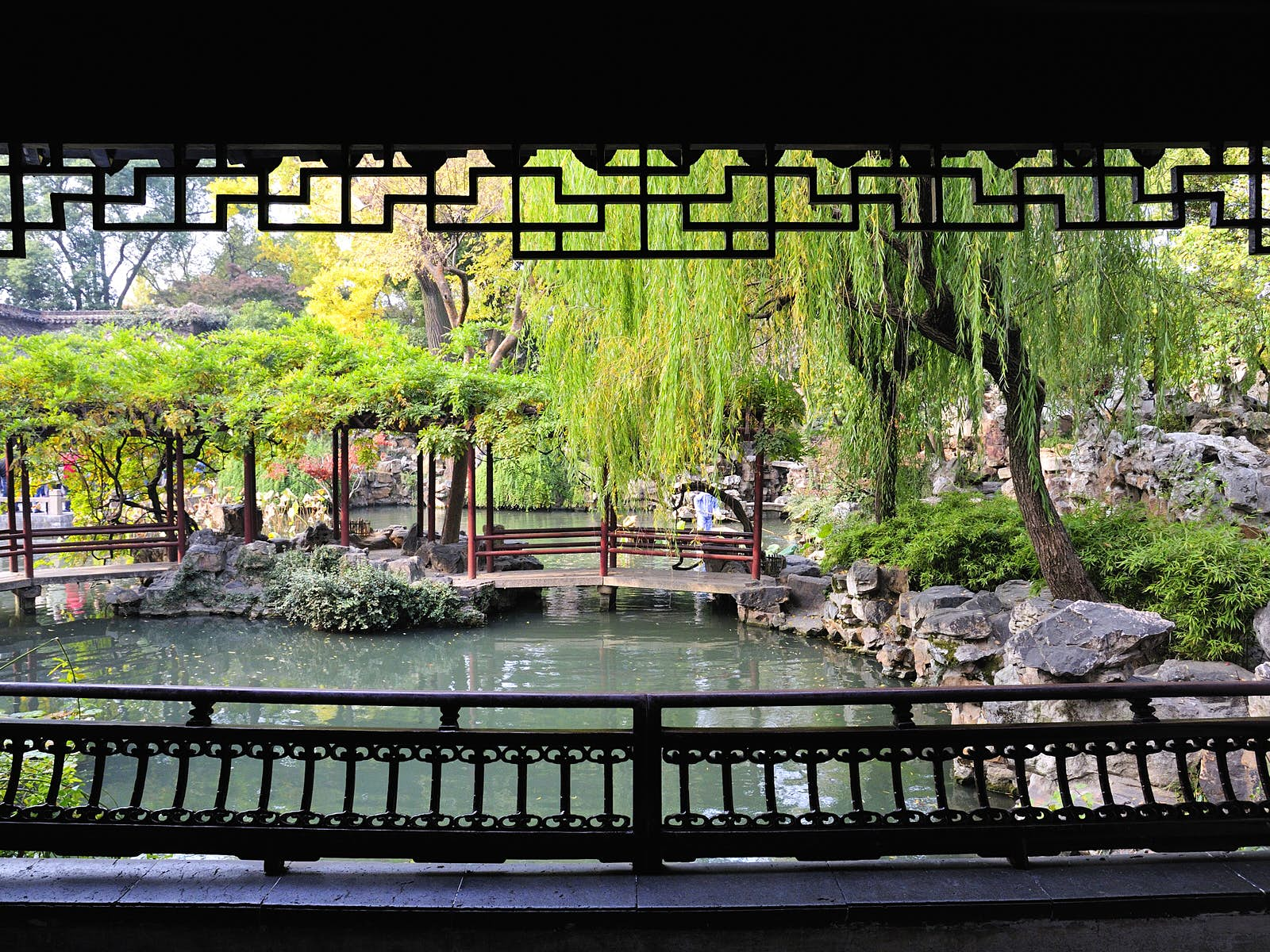 View from inside a covered pavilion, framed by wooden lattice, onto a pond with overhanging willow trees. Visiting a smaller garden at off-peak times is the best way to enjoy its intended tranquility © walkdragon / Shutterstock