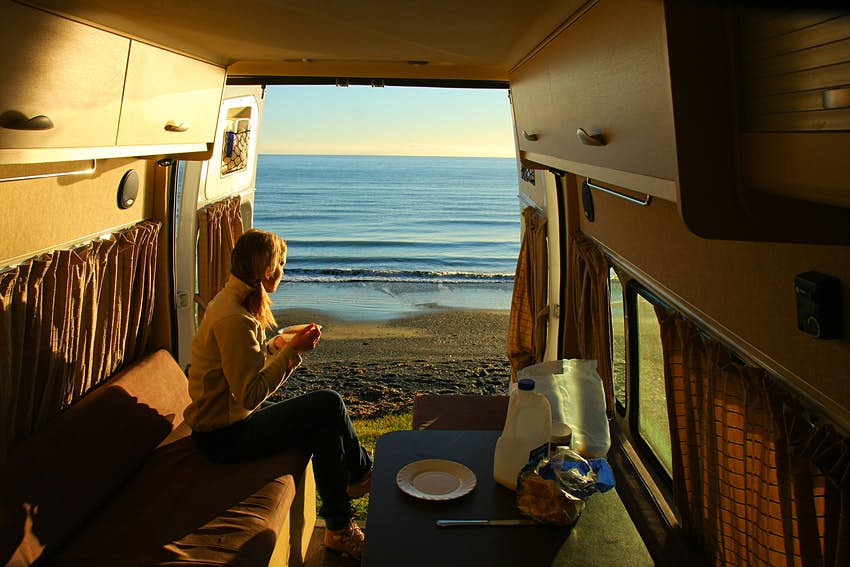 A woman having breakfast in her campervan with the rear door open. The van is parked on a sandy beach, with a very still ocean in the background