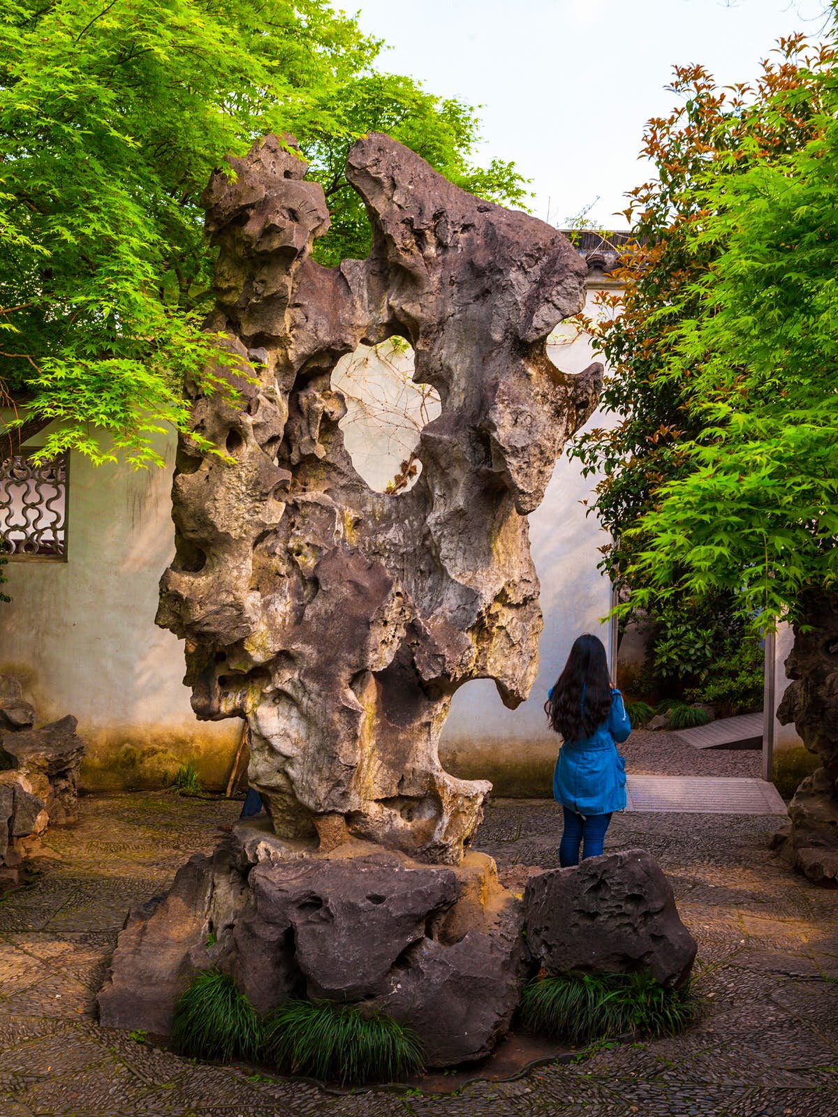 A large, gnarled rock formation with a hole in the middle. The Garden to Linger In is a good place to see giant, bizarrely shaped rock stele © Meiqianbao / Shutterstock