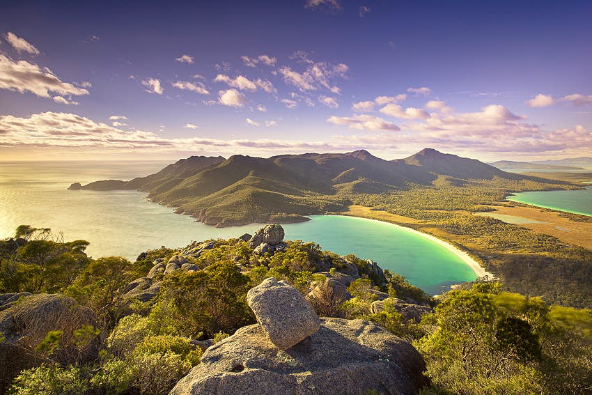 Top of Mt Amos over looking Wineglass Bay, Tasmania at dusk. There are rocks and shrubs in the foreground before giving away to a beautifully smooth beach and blue sea. The sun is low in the sky, throwing out very ambient light.