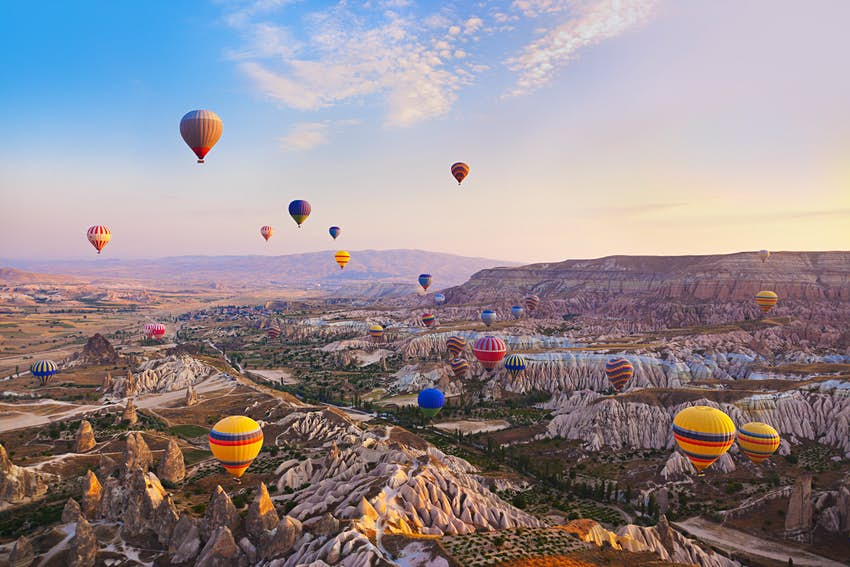 Many colourful hot air balloons flying over a rocky landscape in Cappadocia