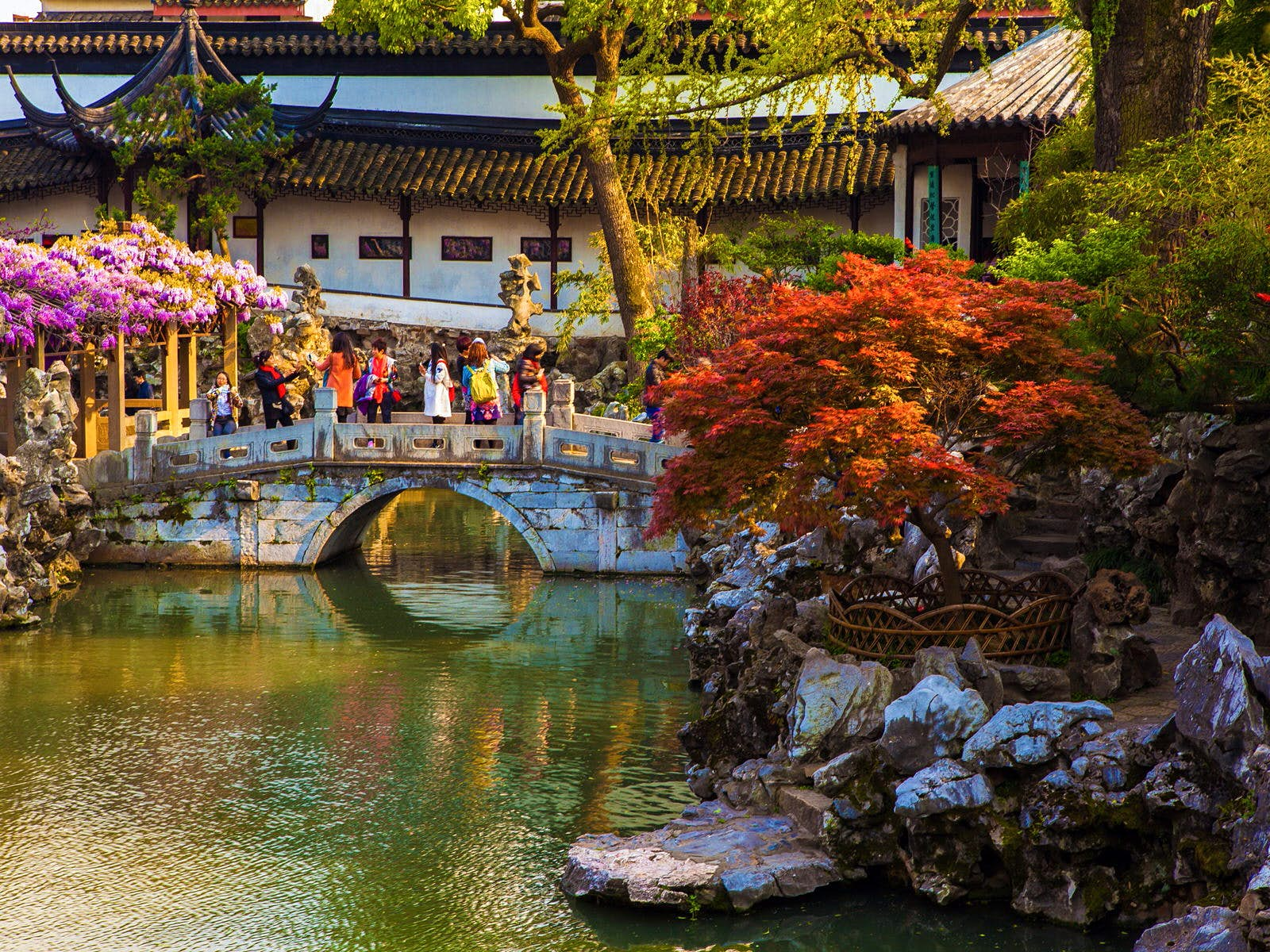 A pond with small stone bridge and covered walkway in the background, framed by red-leafed trees. Classical Chinese landscape architecture – marked by pavilions, covered walkways, rock features and ponds – was developed in Suzhou © Meiqianbao / Shutterstock
