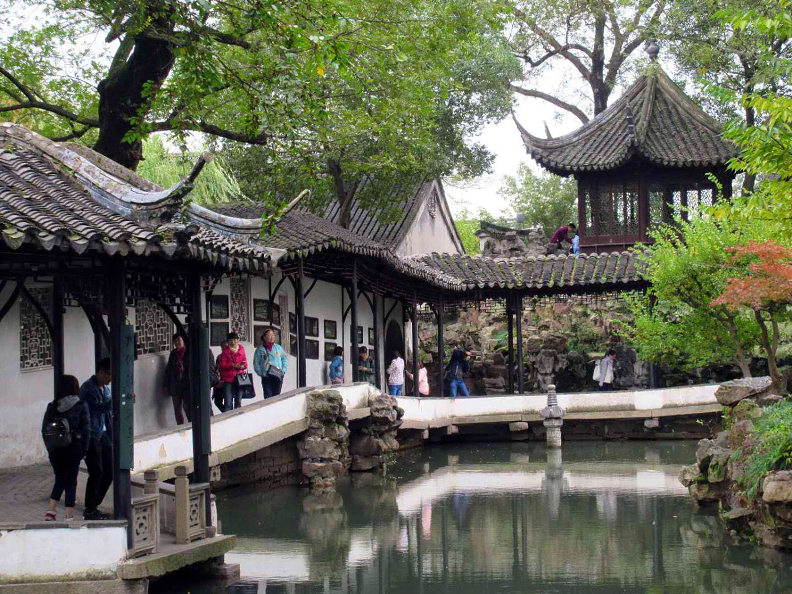 A covered walkway with upturned eaves next to a pond with Chinese pavilion in the background. Suzhou's gardens were first cultivated as private residences © Tess Humphrys / Lonely Planet