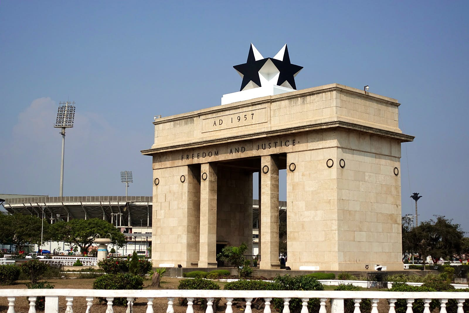 A large, rectangular stone gate, topped by large black stars, stands tall over Independence Square in Accra. The football stadium looms in the distance © Elio Stamm / Lonely Planet