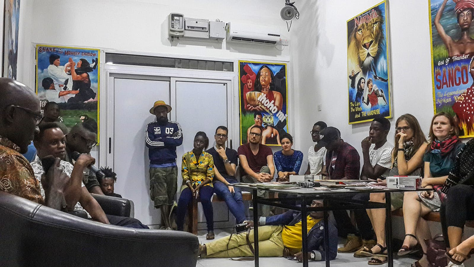 Within a small, stark white room people of African and European descent stand and sit along the walls, even lounging on the floor, while listening to a talk at The Studio © Elio Stamm / Lonely Planet