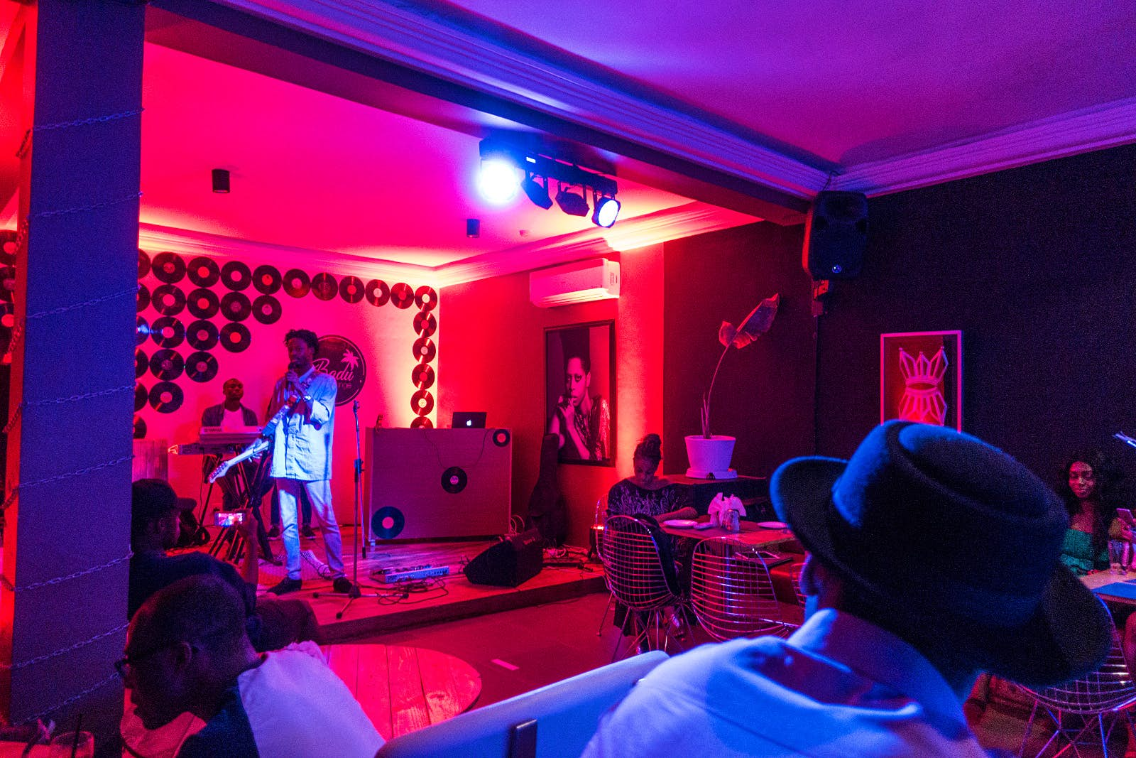 A small stage and room glow red, with a singer on stage holding a guitar and microphone. The back wall of the stage is decorated with a pattern of old vinyl records © Elio Stamm / Lonely Planet