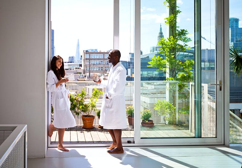 Minimoon magic: a couple in white dressing gowns on a London apartment balcony © izusek / Getty Images
