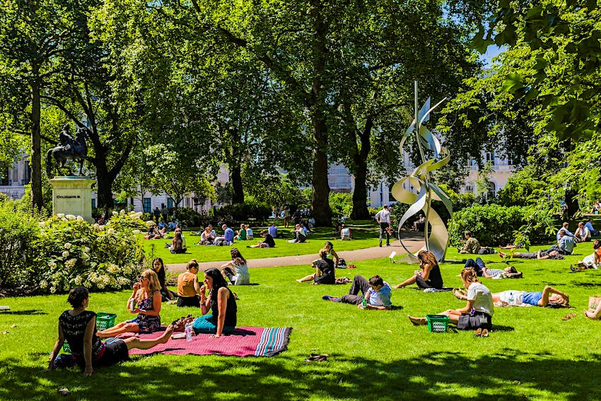People picnicking in a park in London in sunny weather