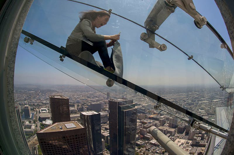 Woman slides down the Skyslide, a 45-foot outdoor glass slide 70 floors up on the outside of the US Bank Tower Woman slides down the Skyslide, a 45-foot outdoor glass slide 70 floors up on the outside of the US Bank Tower © David Mcnew / Getty Images