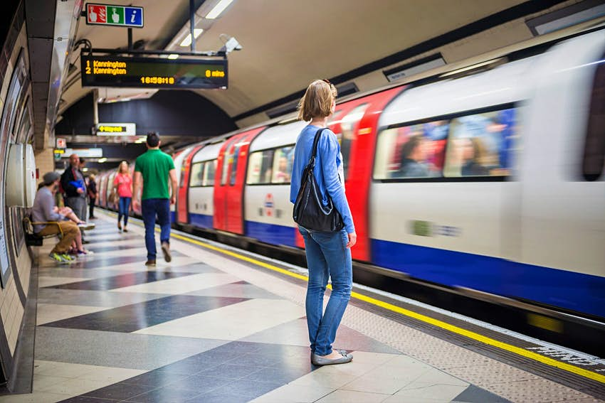 Passengers wait for a Northern Line train at Waterloo Tube station in London