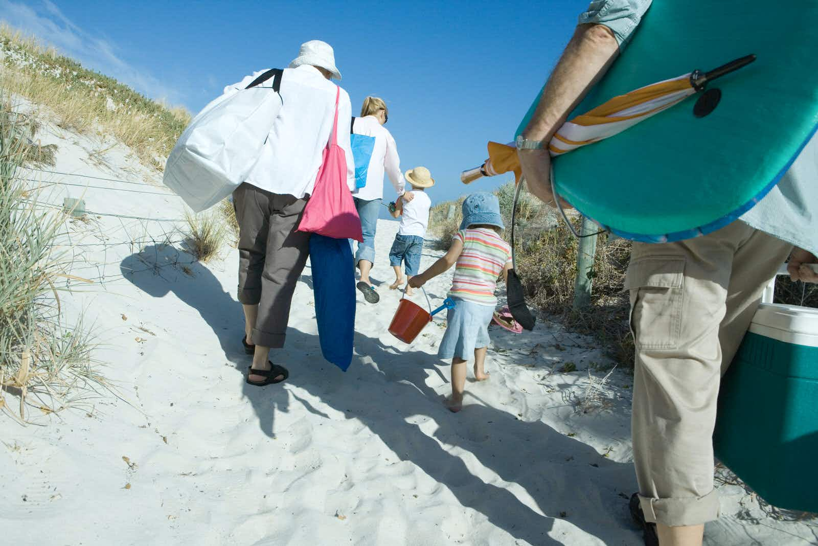 Rear view of a family group of three adults and two young children, make their way through sand dunes carrying a lot of beach items