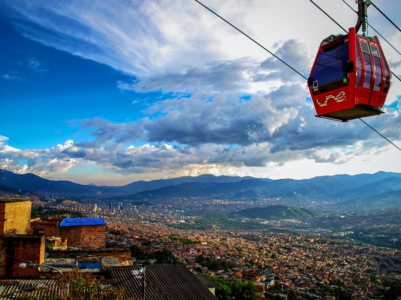 A cablecar passes over a hillside neighborhood of Medellín