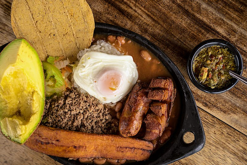 A plate of food with an egg, avocado, plantains, ground beef, arepas, beans and sausage.
