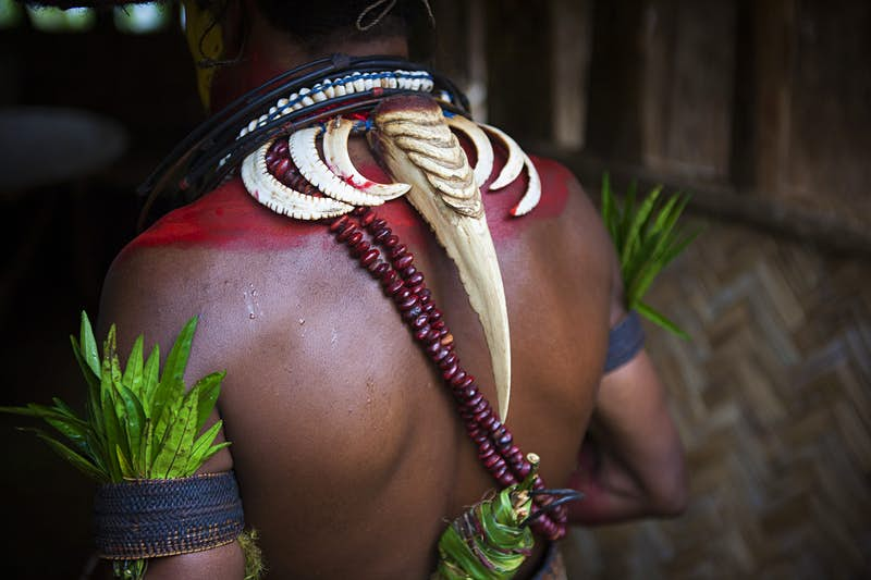 Features - Male Huli wearing a hornbill beak around her neck, Papua New Guinea